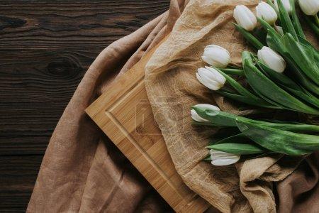 Photo pour Vue de dessus des tulipes de printemps sur la nappe et planche de bois pour la journée internationale de womens - image libre de droit