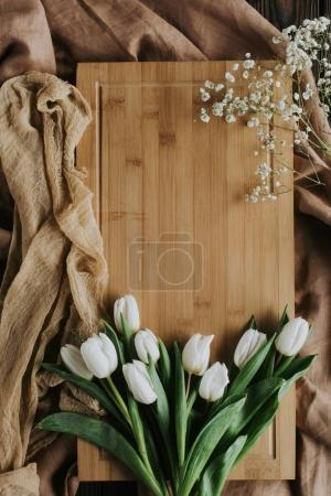 top view of white tulips on wooden board and tablecloth for international womens day