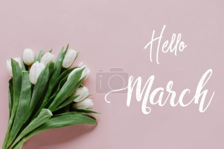 top view of bouquet of white tulips on pink with Hello March lettering