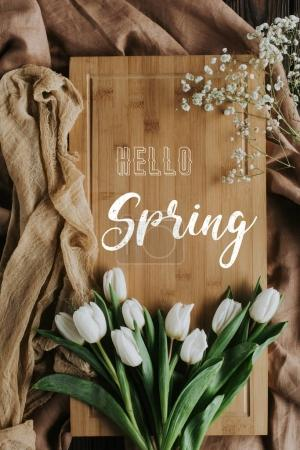 top view of white tulips on wooden board with hello spring lettering