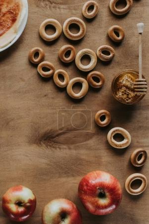 top view of sweet bagels, honey and apples on wooden table