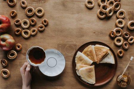 recadrée tir de personne buvant du thé et manger des crêpes à la table en bois