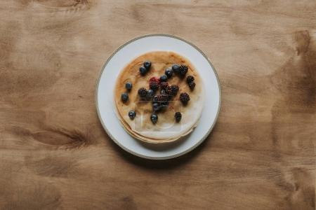 top view of sweet homemade pancakes with healthy berries on wooden table
