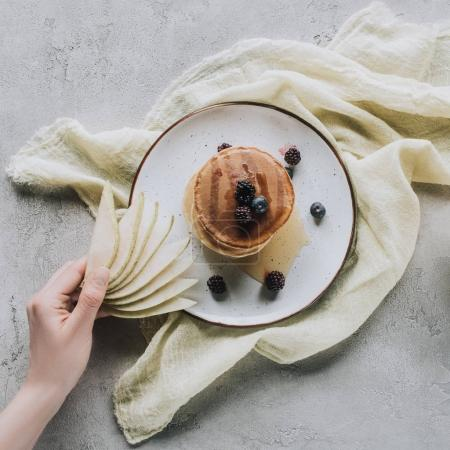 top view of person holding sliced pear above tasty homemade pancakes with berries and honey