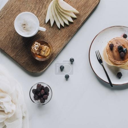 top view of delicious homemade pancakes with berries and honey on grey