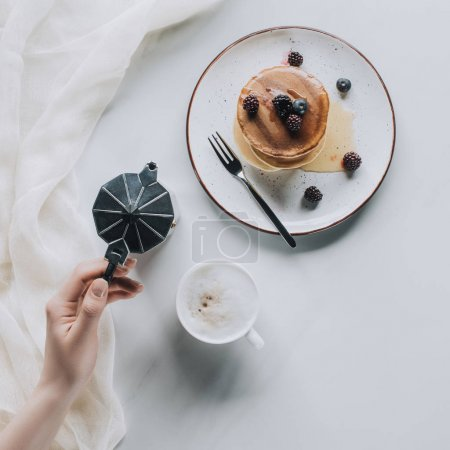 Photo for Top view of person holding coffee pot while eating sweet pancakes with berries for breakfast - Royalty Free Image
