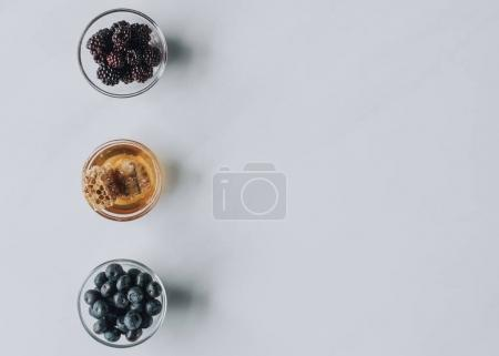 top view of glass bowls with berries and honey isolated on grey