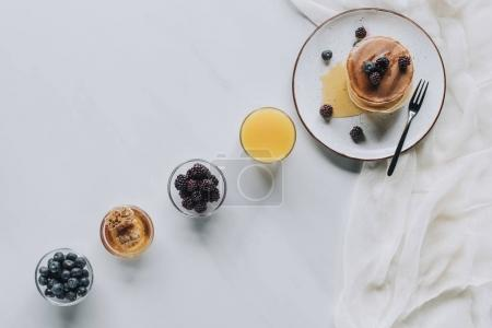 Photo for Top view of tasty breakfast with pancakes, berries, honey and juice on grey - Royalty Free Image