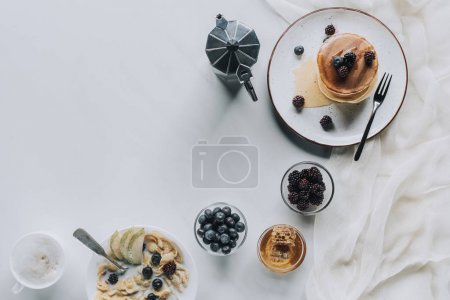 top view of tasty healthy breakfast with pancakes and cappuccino on grey