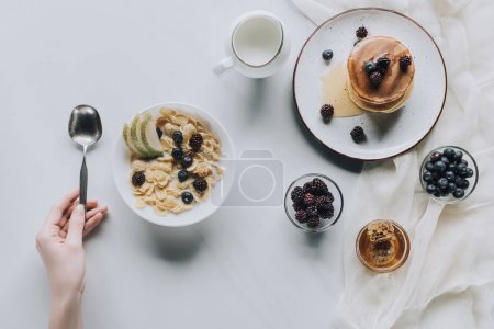 cropped shot of person holding spoon and fresh healthy breakfast on grey
