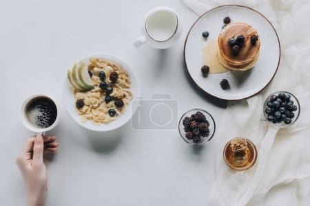 top view of person holding cup of coffee during healthy breakfast