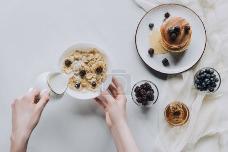 top view of person pouring milk in bowl with muesli during breakfast