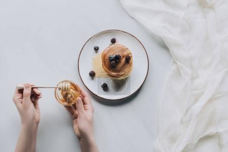cropped shot of person eating delicious homemade pancakes with berries and honey on grey