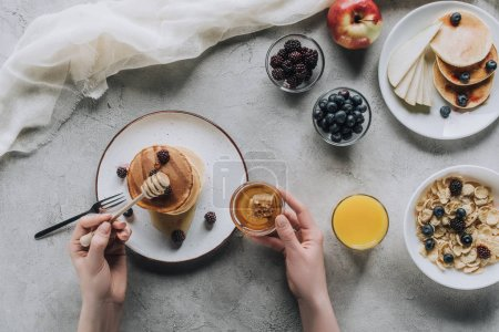 Photo for Cropped shot of person eating delicious homemade pancakes with honey and fruits on grey - Royalty Free Image