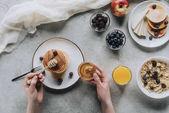 """Постер, картина, фотообои """"обрезанное выстрел, лица, едят вкусные домашние блинчики с медом и фруктами на серый"""""""