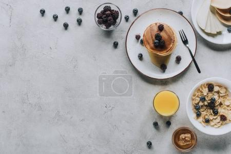 top view of delicious homemade breakfast with pancakes, fruits, honey and muesli on grey