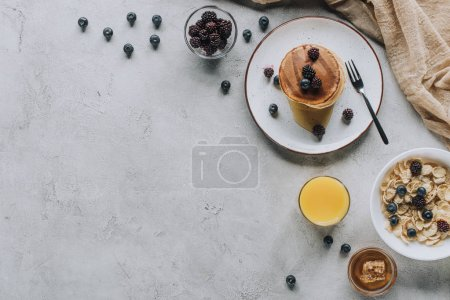 Photo for Top view of tasty healthy breakfast with pancakes, berries, honey and muesli on grey - Royalty Free Image