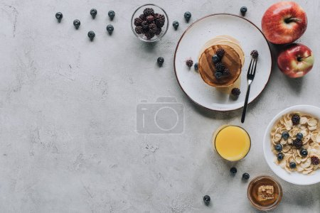 Photo for Top view of tasty healthy breakfast with pancakes, fruits, honey and muesli on grey - Royalty Free Image