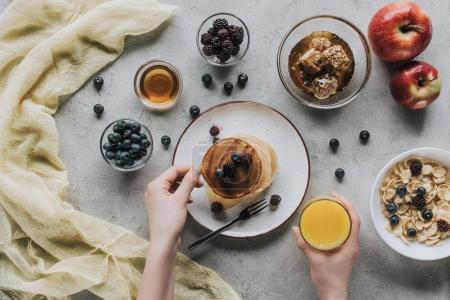 partial top view of person eating healthy breakfast with homemade pancakes, fresh fruits and honey on grey