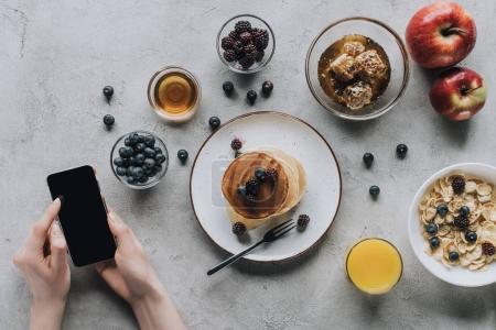 cropped shot of person using smartphone while having healthy tasty breakfast