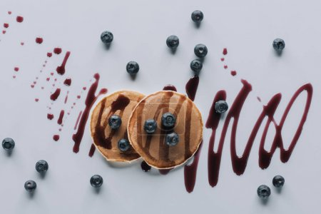 top view of delicious pancakes with fresh blueberries and jam on grey