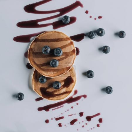 top view of tasty pancakes with fresh blueberries and jam on grey