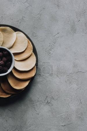 top view of fresh sweet pancakes with blackberries on grey