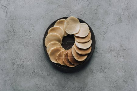 top view of tasty homemade pancakes on plate on grey