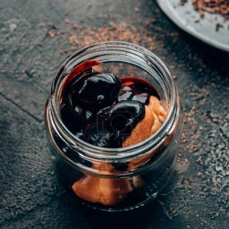 Photo for Close-up view of sweet delicious homemade chocolate dessert in glass jar on black - Royalty Free Image