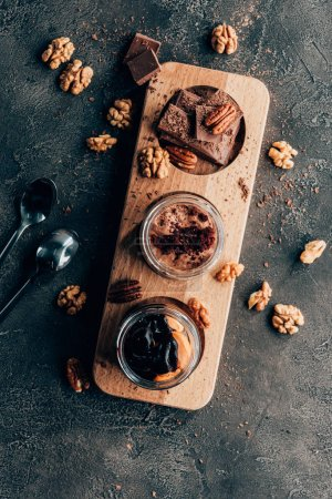 Photo for Top view of sweet tasty chocolate desserts with nuts on black - Royalty Free Image