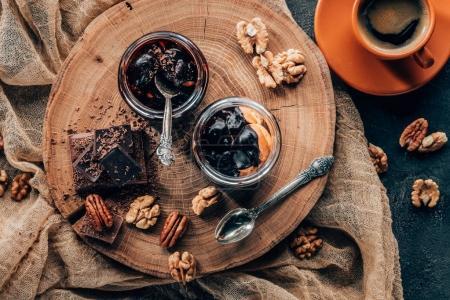 Blick von oben auf köstliches Dessert in Glasgläsern und Schokoladenstücken mit Nüssen und Tasse Kaffee