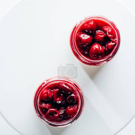 top view of sweet healthy cherry dessert in glass jars on white