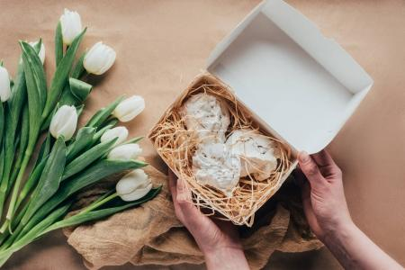 cropped shot of person holding box with delicious meringue cookies and white tulips