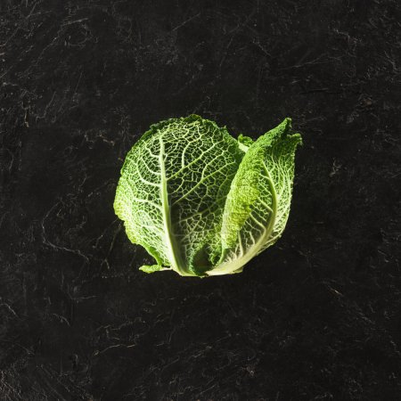 top view of fresh healthy organic savoy cabbage on black