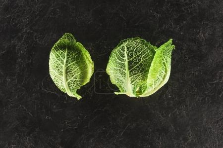 top view of fresh healthy green savoy cabbage on black