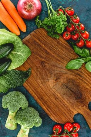 top view of fresh healthy raw vegetables and wooden cutting board