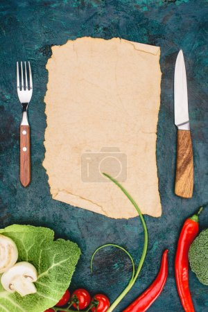 top view of blank parchment, fork with knife and raw vegetables on black