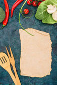 top view of blank parchment, wooden utensils and ripe raw vegetables on black