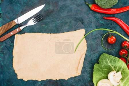 top view of blank parchment, fork with knife and ripe raw vegetables on black
