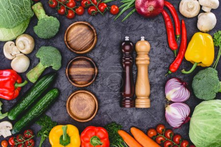 top view of fresh organic vegetables, wooden plates and containers for spices on black