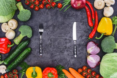 top view of fresh organic assorted vegetables and fork with knife on black