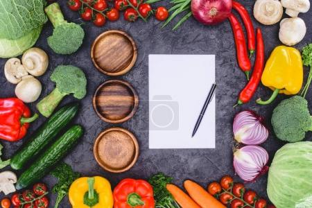 Photo for Top view of three empty wooden plates, blank paper with pen and fresh assorted vegetables on black - Royalty Free Image