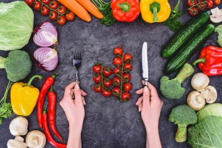 cropped shot of person holding fork and knife above healthy fresh vegetables on black