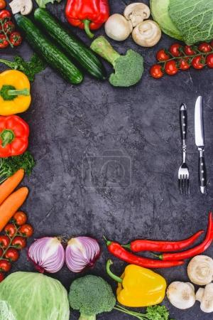 top view of fresh healthy organic vegetables and fork with knife on black