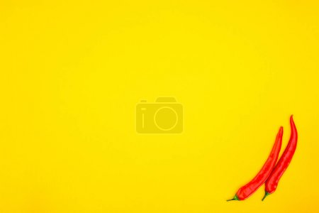 top view of raw red chili peppers isolated on yellow background