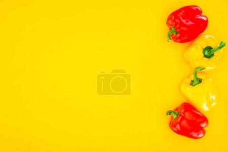 top view of fresh raw organic peppers isolated on yellow