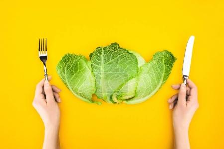 top view of person holding fork and knife while eating healthy cabbage isolated on yellow
