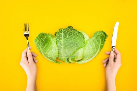 Photo for Top view of person holding fork and knife while eating healthy cabbage isolated on yellow - Royalty Free Image