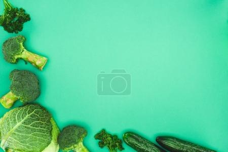 top view of fresh raw broccoli, parsley, cucumbers and savoy cabbage isolated on green background