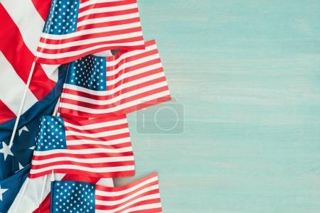 Photo for Top view of arranged american flags on blue wooden tabletop, presidents day concept - Royalty Free Image